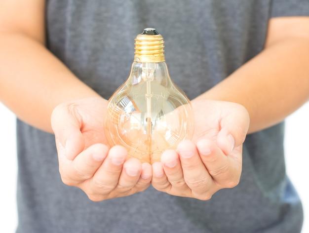Led電球(ランプ)を手に白い背景に分離
