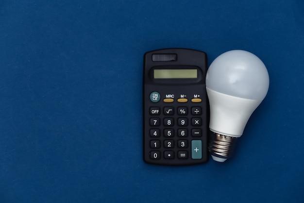 古典的な青い背景の電卓とled電球。エネルギーを節約します。カラー2020。上面図