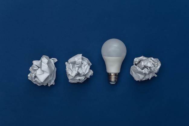 古典的な青い背景のしわくちゃの紙のボールとled電球。エココンセプト。カラー2020。上面図