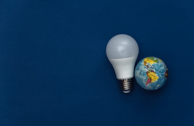 Led light bulb with globe on classic blue background. eco concept. save planet. color 2020. top view
