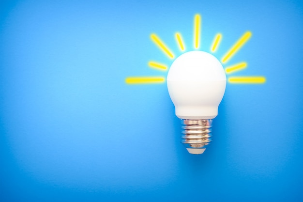 Led light bulb with yellow rays on blue background