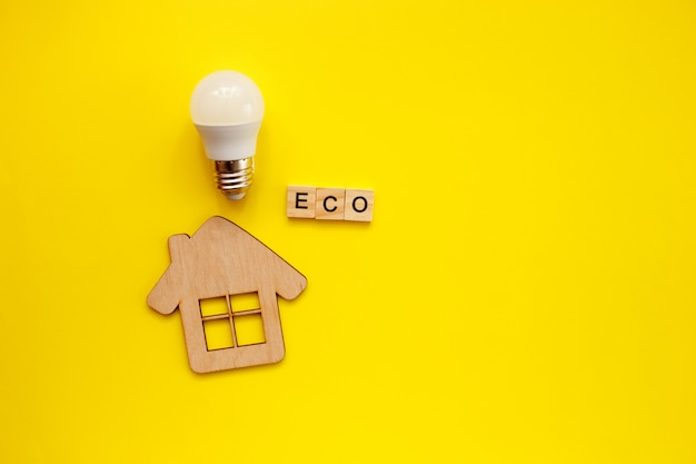 Led light bulb and wooden house on yellow
