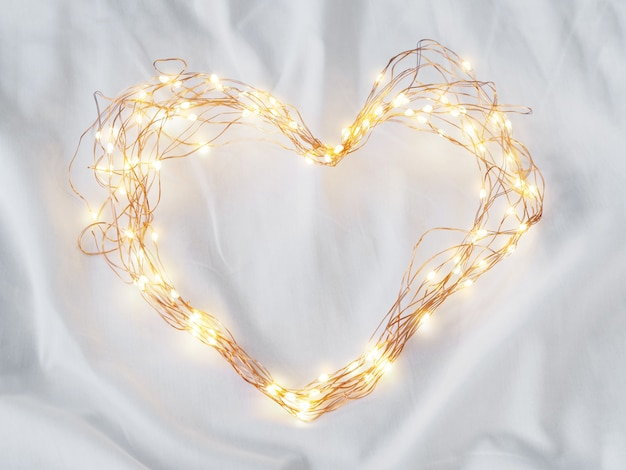 Led lighting and wire frame heart shape on white bedsheet