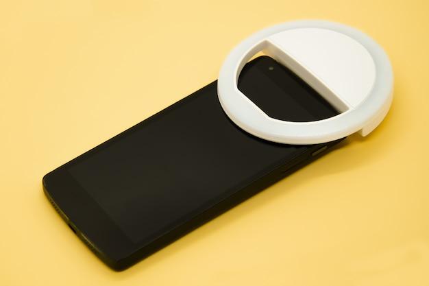 파스텔 노란색 배경에 스마트 폰에 led selfie 원형 링 조명 램프. 셀카 사진을 찍을 수있는 클립 온 플래시 라이트 카메라 폰. 블로거 및 동영상 블로거를위한 소형 장치입니다. 선택적 초점
