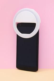 분홍색 노란색 배경에 스마트 폰에 led selfie 원형 링 조명 램프. 셀카 사진을 찍을 수있는 클립 온 플래시 라이트 카메라 폰. 블로거 및 동영상 블로거를위한 소형 장치입니다. 세로 샷