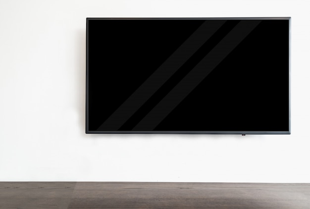 Led smart tv hanging on the white wall background,with wood table.