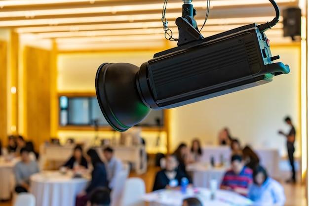 Светодиодный прожектор в зале семинара с размытыми людьми позади.