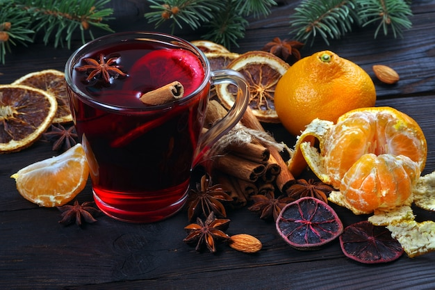 Led wine, spices and citrus fruits on a wooden table.