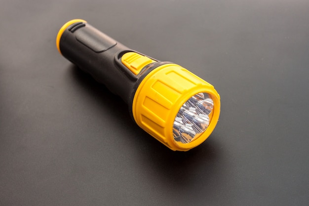 Led yellow flashlight on black background