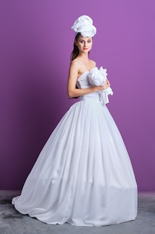 Ledライトテープで飾られた長いウェディングドレスと帽子の美しい花嫁の完全な長さの肖像画
