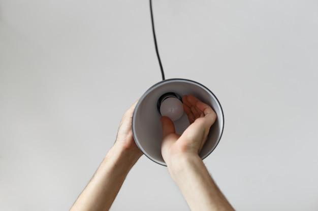 黒い色でフロアランプのled電球の電球を変更します。明るい灰色の背景に