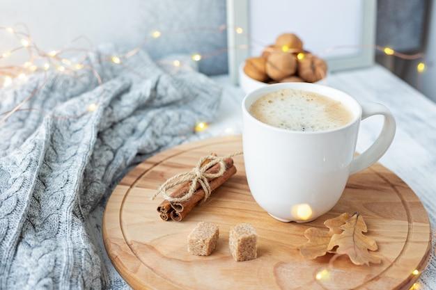 コーヒーマグカップ、セーター、シナモン、ledライトで飾られた居心地の良い秋の組成