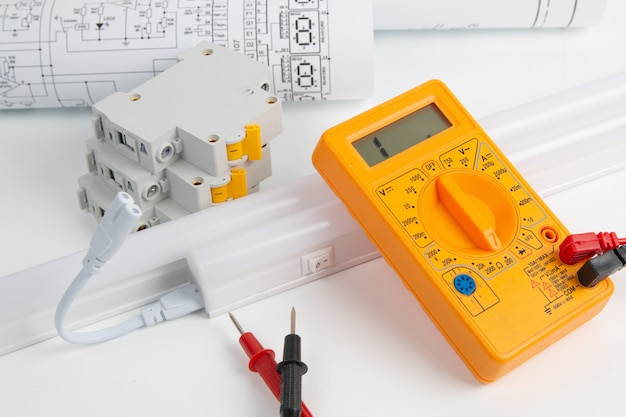 回路ブレーカー、図面、ledランプ、デジタルマルチメーター、白いテーブル
