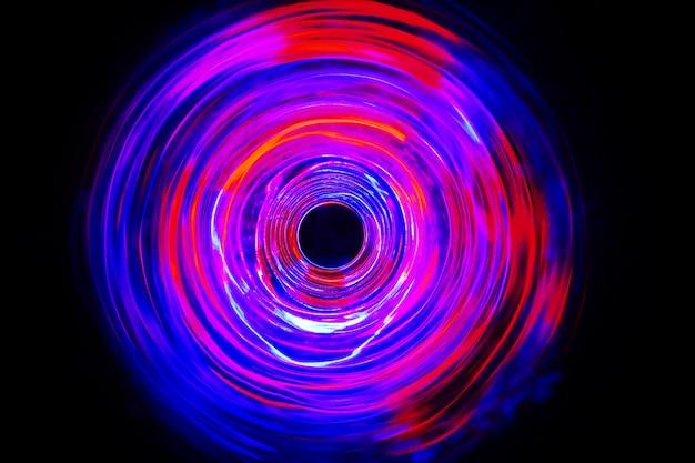 長時間露光で動くled赤と青の光が暗闇の中で撮影。