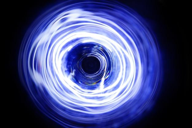 長時間露光で移動するledの青と白の光が暗闇の中で撮影。