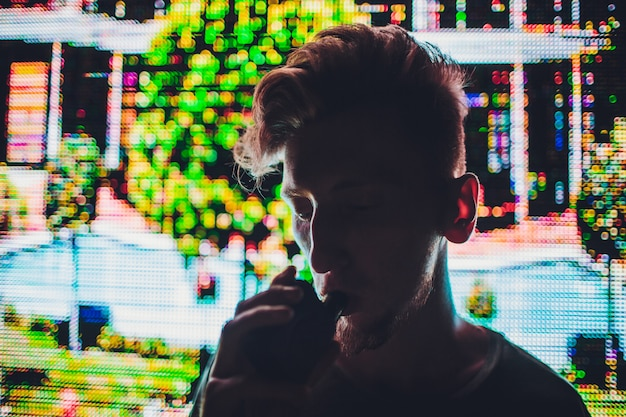 Ledから不明瞭な色の帯で路上で電子タバコを喫煙の成熟した男の肖像画