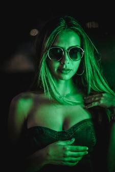 緑のledライトに照らされた黒いドレスを着た白人ブルネットは、黒い結晶に反射しました。都市の夜の写真。クローズアップの肖像画