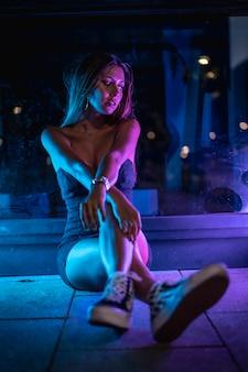 紫と青のledライトに照らされた黒いドレスを着た白人ブルネットは、床に座って右を向いている黒い結晶に反射しました。夜の都市写真