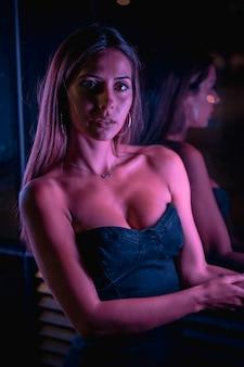 カメラを見て、紫色のledライトに照らされた黒いドレスを着た若いブルネットの白人女性。夜の都市写真