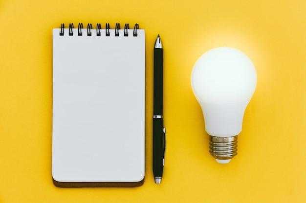 黄色の背景に空のノートブックを開く、ペンとled電球のトップビュー