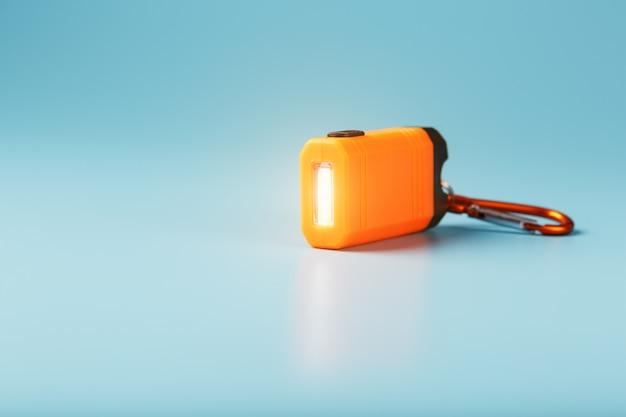 青色の背景にオレンジ色のled懐中電灯とカラビナが光っています。
