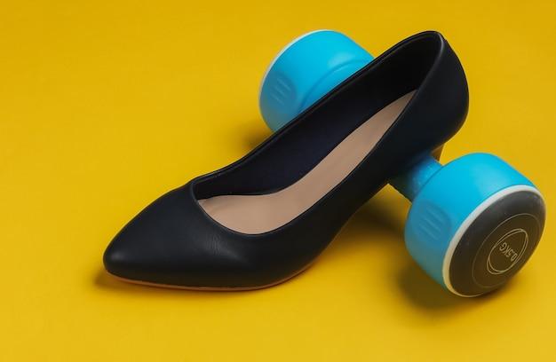 Leddysスポーツレディースハイヒールの靴黄色の背景にダンベルフィットネスとファッションのコンセプト