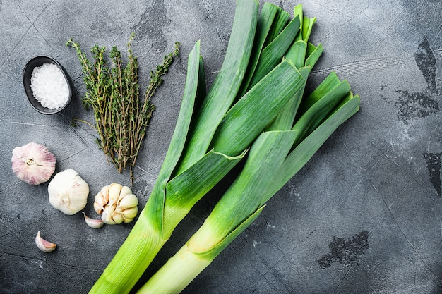 Leek stalks on  with herbs ingredients for coocing braised leeks, on grey textured table top view with space for text.