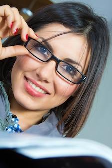 Leer revista morena gafas elegante
