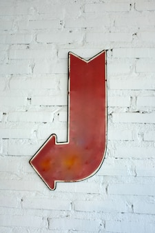 Left arrow sign on white brick wall, block background with arrow sign