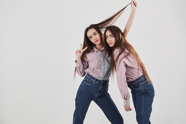 Левая девушка показывает жест двух пальцев. две сестры-близнецы стоят и позируют