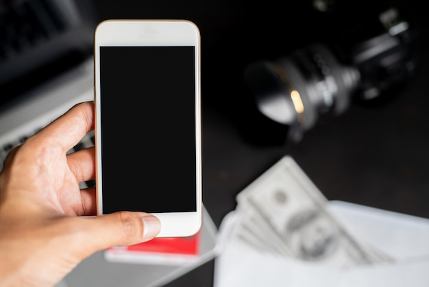 Left hand holding smartphone on blur blackground with laptop, dollars, camera, and credit card