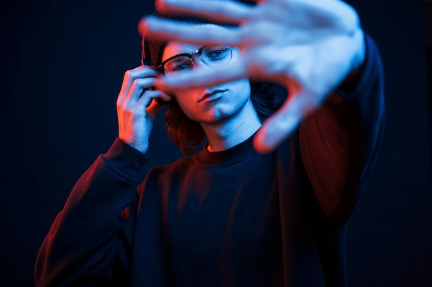 Left hand is blurred. studio shot in dark studio with neon light. portrait of serious man