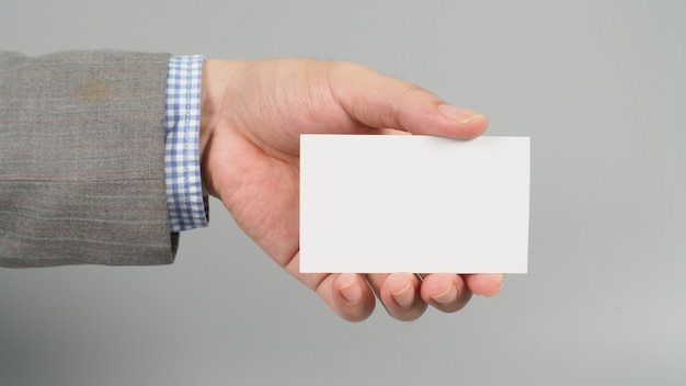 Левая рука держит белую пустую карточку и носит костюм на сером фоне. концепция делового человека