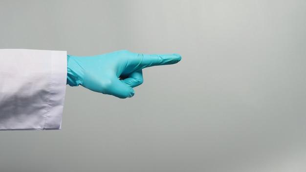 왼손은 손가락을 가리키고 회색 배경에 격리된 의사 가운과 함께 파란색 의료 장갑을 착용합니다. 스튜디오 촬영.