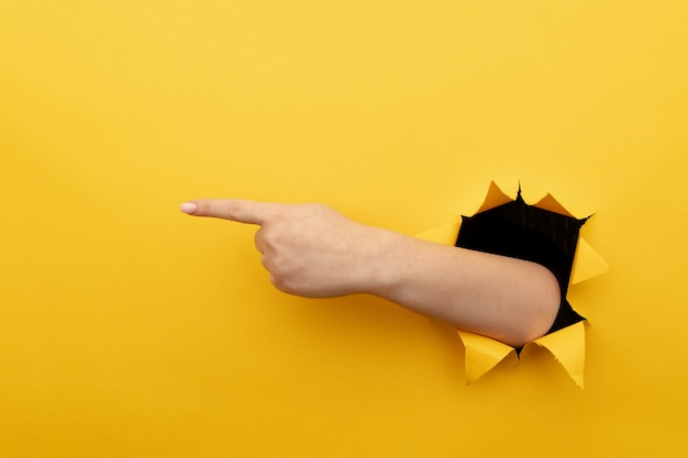 黄色の背景を通して右を指している左手。