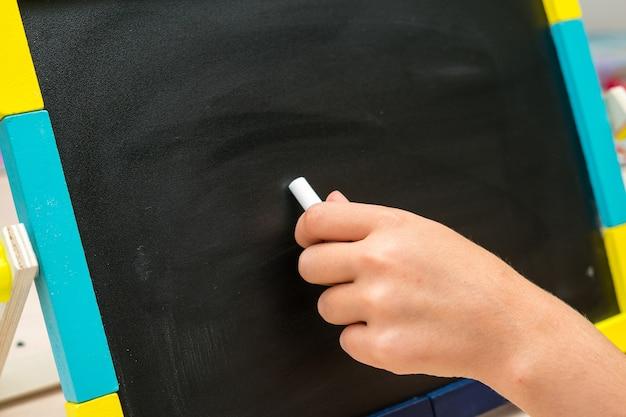 Левая рука писать на школьной партой на черном фоне