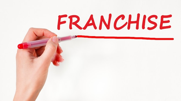 Left hand writing inscription franchise with red color marker, concept, stock image