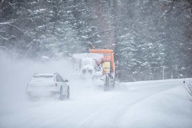Left-handed driving road maintenance truck clears snow from the road in the forest with a car driving behind it.