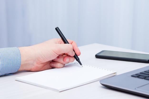 左利きの男性がノートに書き込む