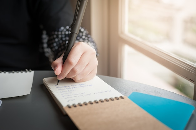 Left-handed woman with pen writing on notepad