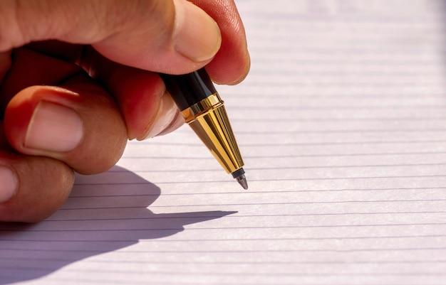 흰색 줄이 그어진 종이에 얕은 초점으로 금색 펜으로 왼손 쓰기