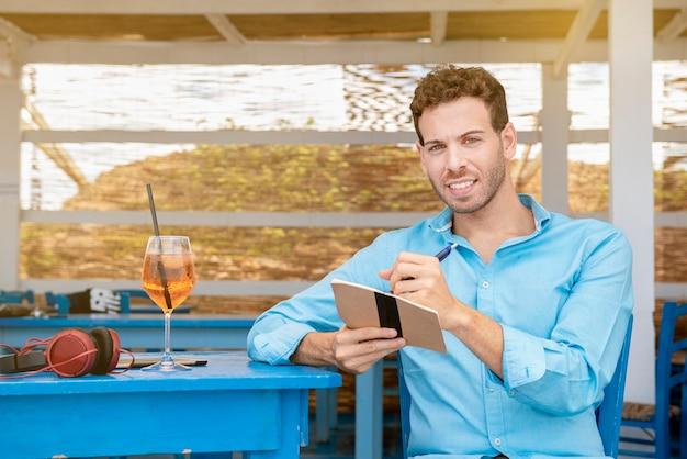 ビーチバーに座って、屋外でスマートに働くという宿題のコンセプトを書いている左利きの若い男