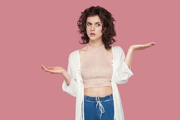 Влево или вправо? портрет сомнительной красивой молодой женщины брюнет с вьющейся прической в непринужденном стиле стоя, поднял руки и смущен для выбора. крытая студия выстрел, изолированные на розовом фоне.