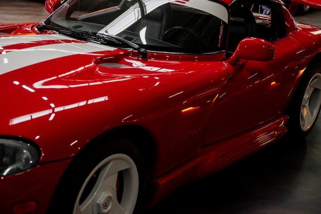 車両展示会で屋内に立っている赤いスポーツカーの左側