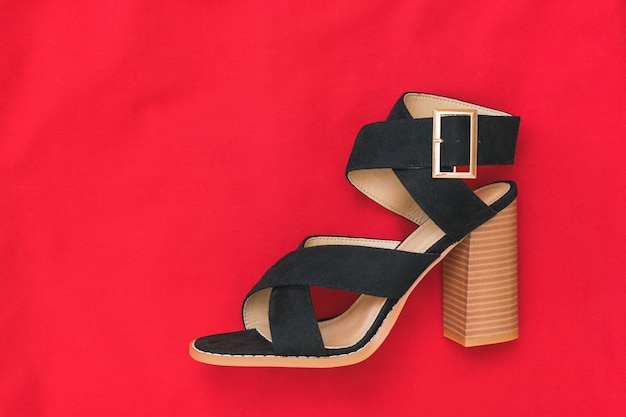 Left women's suede shoe on a surface of bright red fabric