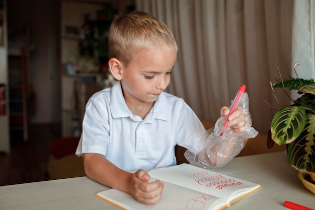 Lefthanded boy put his left hand in plastic glove to avoid messy international lefthander day