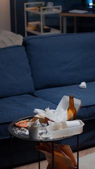 散らかったリビングルームのテーブルにピザの空のビール瓶とナプキンの残り物