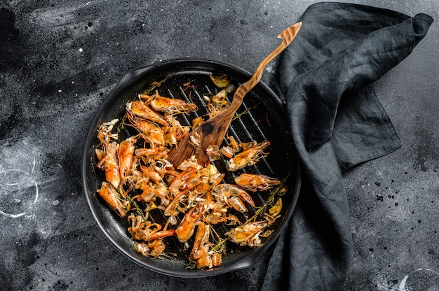 Leftover shrimps, prawns in pan. waste food peeled, detail of the heads. top view. copy space