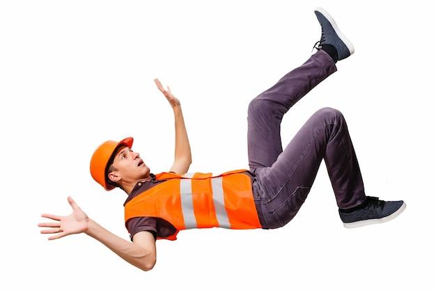 직장에서 부상당한 누워있는 작업자의 다리와 노란색 헬멧.