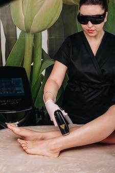 Процедура лазерной эпиляции ног, сделанная в косметологической клинике молодой женщине